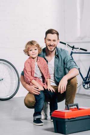 happy man sitting with little son near tools box at bicycle workshop