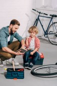 happy man pointing by hand at book to little son sitting on tools box in bicycle workshop