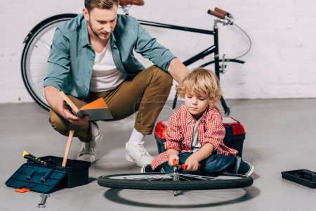 selective focus of man with book sitting near little son fixing bicycle wheel with pliers in workshop