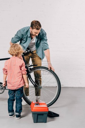 father showing little son how to fixing bicycle near tools box in workshop