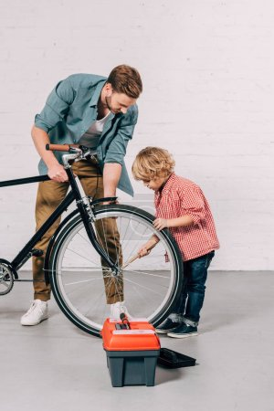 selective focus of boy and his father repairing bicycle wheel in workshop