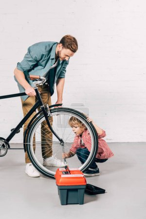 child and his father repairing bicycle wheel near tools box in workshop