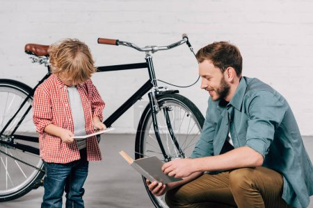 boy using digital tablet while father reading book near bicycle