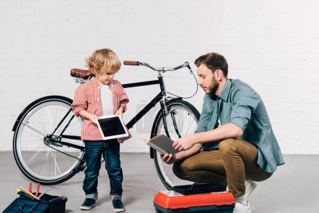 little child with digital tablet and father reading book at bicycle workshop