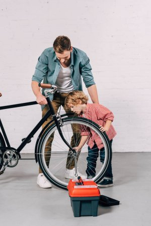 little boy and his father repairing bicycle wheel in workshop