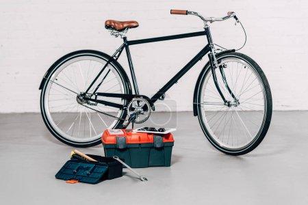 Photo pour Mise au point sélective de bicyclette près de boîtes à outils avec tablette numérique en atelier - image libre de droit