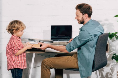 Photo for Side view of man giving book to little son near table with laptop at home - Royalty Free Image