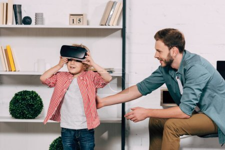 curly boy putting on virtual reality headset while his father sitting near at home