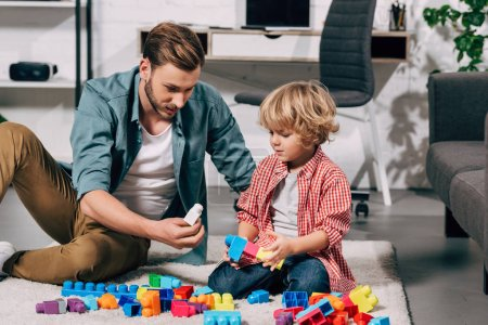 Photo for Curly boy and his father playing with colorful plastic blocks on floor at home - Royalty Free Image