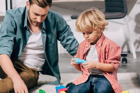 Photo for Close up view of kid and his father playing with colorful plastic blocks on floor at home - Royalty Free Image