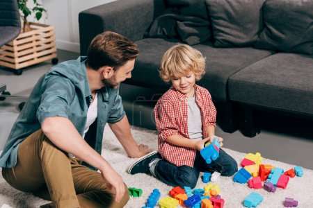 Photo for High angle view of happy child and his father playing with colorful plastic blocks on floor at home - Royalty Free Image