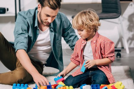 Photo for Selective focus of child and his father playing with colorful plastic blocks on floor at home - Royalty Free Image