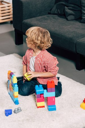 Photo for High angle view of curly little kid playing with colorful plastic blocks on floor at home - Royalty Free Image