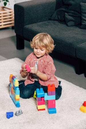 curly little boy playing with colorful plastic blocks on floor at home