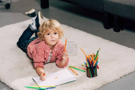 high angle view of adorable little boy drawing by marker at home