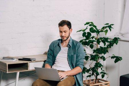 Photo pour Jeune beau mâle pigiste travaillant sur ordinateur portable à la maison - image libre de droit