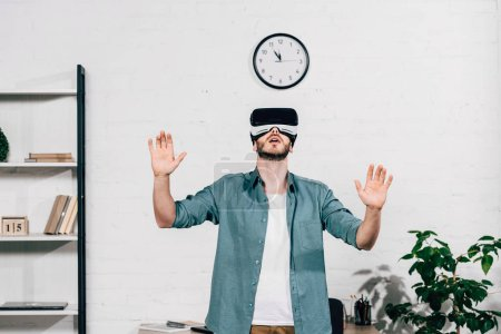 selective focus of young man with wide arms using virtual reality headset at home
