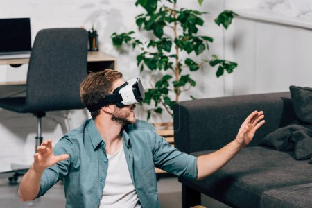 selective focus of young man using virtual reality headset at home