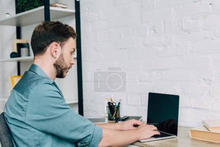 Photo pour Vue latérale de freelance masculin travaillant sur ordinateur portable à la table - image libre de droit