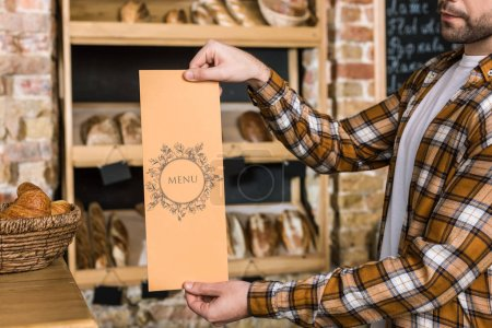 male seller holding paper menu in hands at bakery
