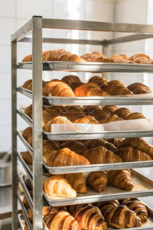 golden french croissants on baking trays at kitchen rack