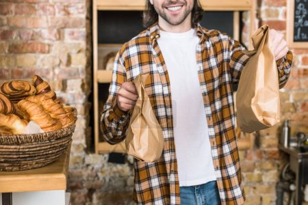 Photo for Smiling man holding paper bags with pastry at bakery - Royalty Free Image