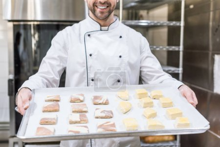Photo for Cropped view of smiling cook holding baking tray with raw dough - Royalty Free Image