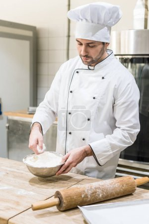 Photo for Adult male baker scattering flour on wooden board at kitchen - Royalty Free Image