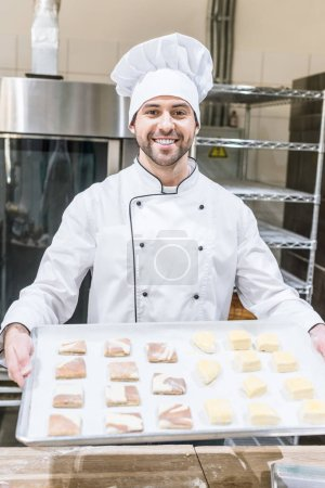 smiling baker in chefs uniform holding baking tray with raw dough pieces