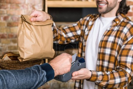 Photo for Cropped view of smiling seller holding paper bag while customer paying for purchase with credit card - Royalty Free Image