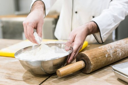 Photo for Close up of baker holding bowl of flour at wooden counter - Royalty Free Image