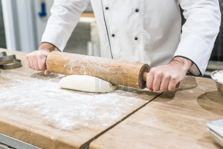 Photo for Close up of chef hands rolling out dough on wooden table - Royalty Free Image