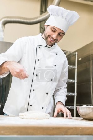 Photo for Baker in white chefs uniform smiling and cooking dough in professional kitchen - Royalty Free Image