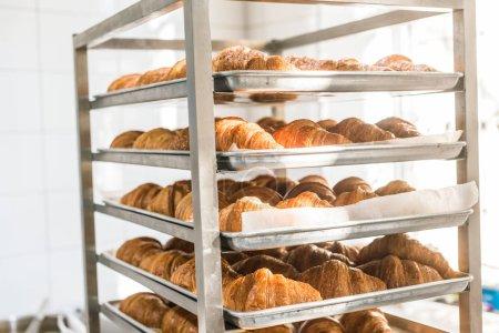 Photo for Rack full of fresh tasty croissants in bakehouse - Royalty Free Image