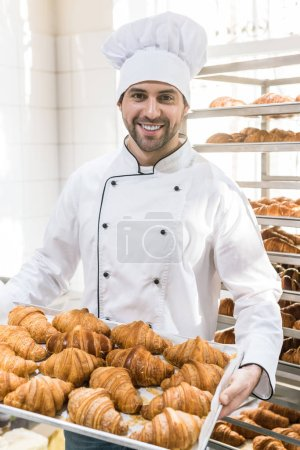 Smiling baker in white chefs uniform with tray full of fresh croissants