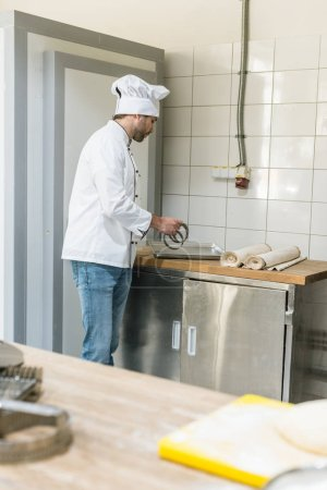 chef in white uniform with cooking utensils at bakehouse kitchen