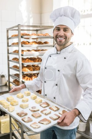 Smiling baker with tray of uncooked dough in bakehouse