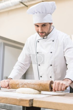 Photo for Chef rolling out dough with rolling pin on wooden table - Royalty Free Image