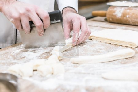 Photo for Close up of baker hands cutting dough on wooden table - Royalty Free Image
