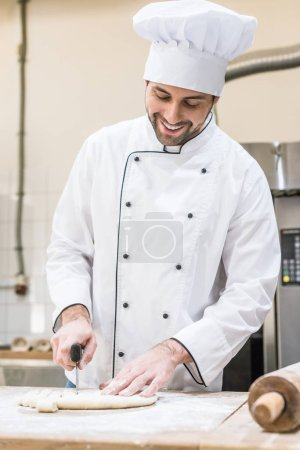 Photo for Handsome baker smiling and cutting uncooked dough on wooden table - Royalty Free Image