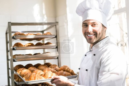 Smiling baker holding tray with fresh cooked croissants in bakehouse