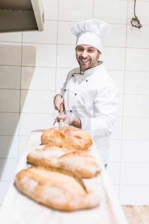 Smiling chef taking out loaves of bread in bakery