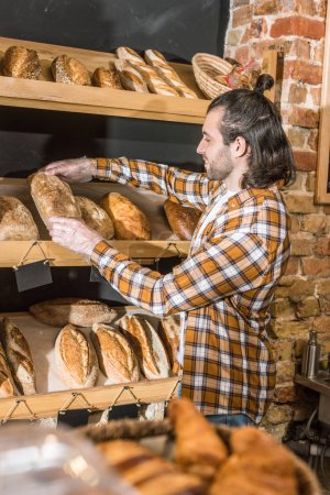 Side view of male seller putting freshly baked bread on wooden shelf