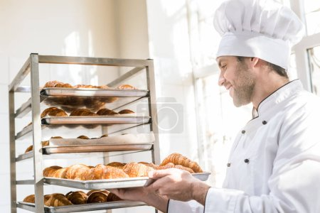 Photo for Side view of smiling baker taking tray with pastry - Royalty Free Image