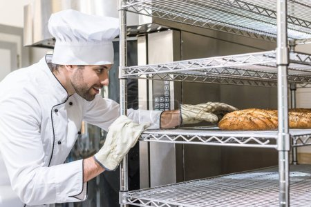 Side view of baker in gloves taking bread
