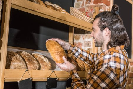 Photo for Side view of seller taking freshly baked bread in hands - Royalty Free Image