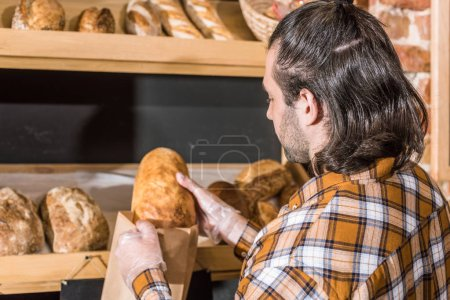 Male seller putting fresh bread in paper bag