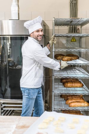 Photo for Side view of smiling chef taking out rack with bread - Royalty Free Image