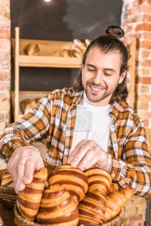 Handsome seller putting pastry in wicker basket