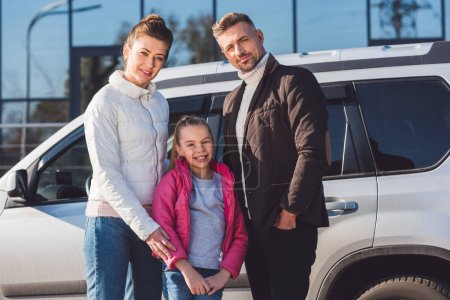 Preteen daughter standing with mom and dad near car